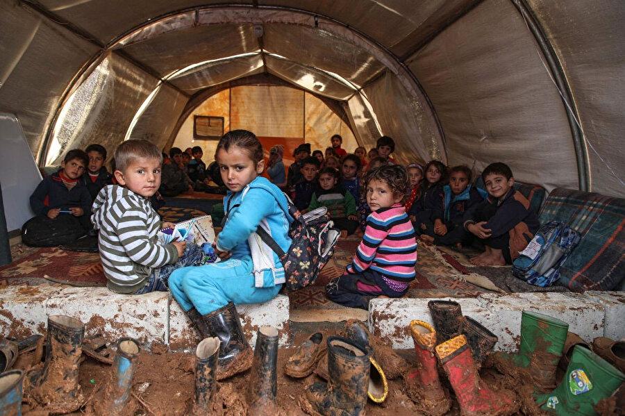 Suriyeli çocuklar, 1 Aralık 2018'de İdlib ilinin kuzey kırsalındaki Sarmada kasabası yakınlarında mülteciler için hazırlanan bir kampta, sınıf olarak kullanılan bir çadırda ders görüyor.