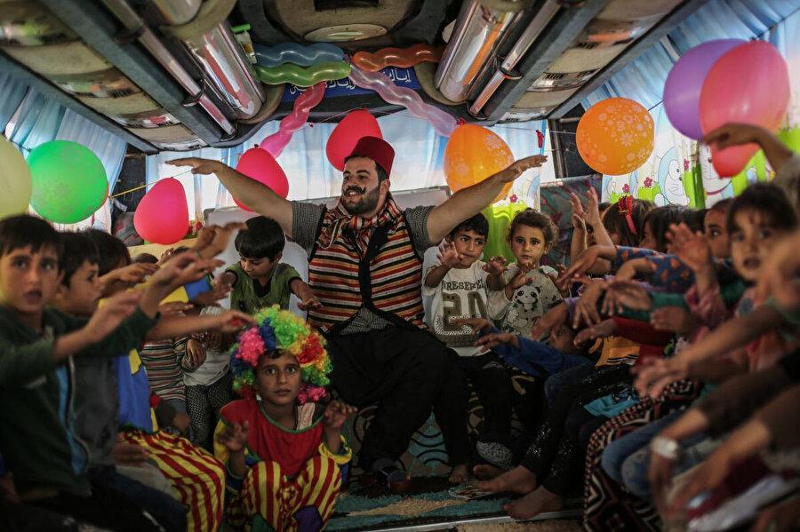 22 Eylül 2019, Suriye, Hazano: Suriyeli bir öğretmen, sınıfa dönüştürülen otobüsün içinde öğrencilerle interaktif bir oyun oynuyor.