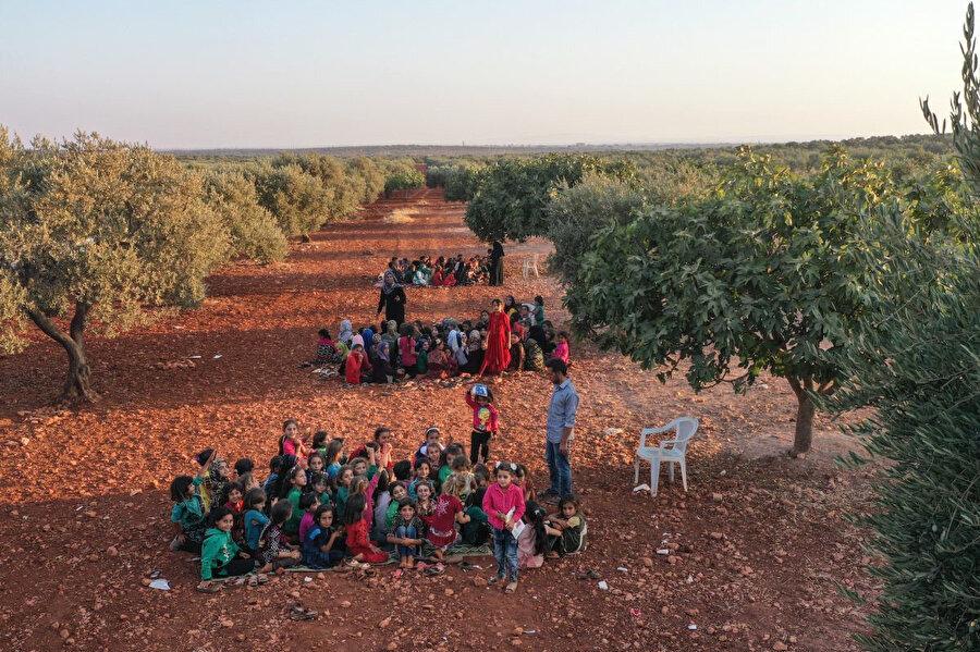 18 Eylül 2019'da Suriyeli çocuklar, İdlib kentine bağlı Killi köyünde açık havada, zeytin ağaçlarının altında ders dinliyorlar.