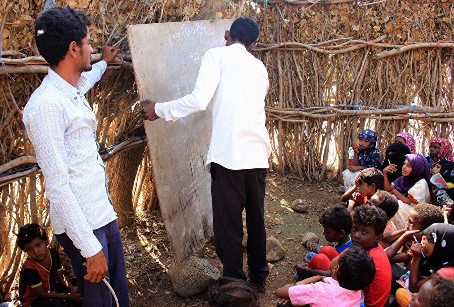 Çatışmalar sebebiyle yerinden edilmiş öğrenciler, Yemen'in kuzeybatısındaki Hacca ilinde, ağaç parçalarından inşa edilen derme çatma okullarında ders görüyorlar.