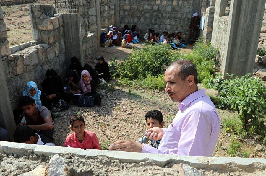 Yemenli bir öğretmen, 16 Eylül 2019'da eğitim öğretim yılının başlangıcında Taiz vilayetine bağlı bir köyde henüz inşaatı bitmemiş okulda üstü açık sınıflarda ders anlatıyor.