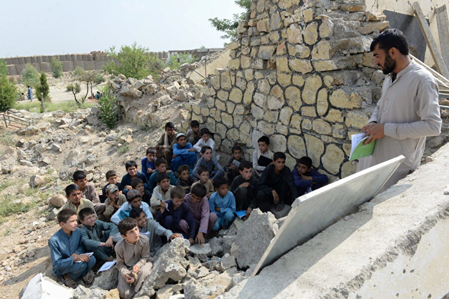 22 Temmuz 2019, öğrenciler, Afganistan'ın Nengrehar vilayetinin Deh Bala bölgesinde Papen Lisesi'nden geriye kalan yıkıntıların arasında ders görüyor.