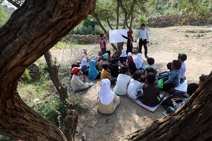 16 Eylül 2019'da Yemen'in Taiz vilayetine bağlı bir köyde çekilen bu fotoğrafta henüz inşaatı tamamlanmamış okullarının yakınında bir ağacın gölgesinde ders işleyen çocuklar.