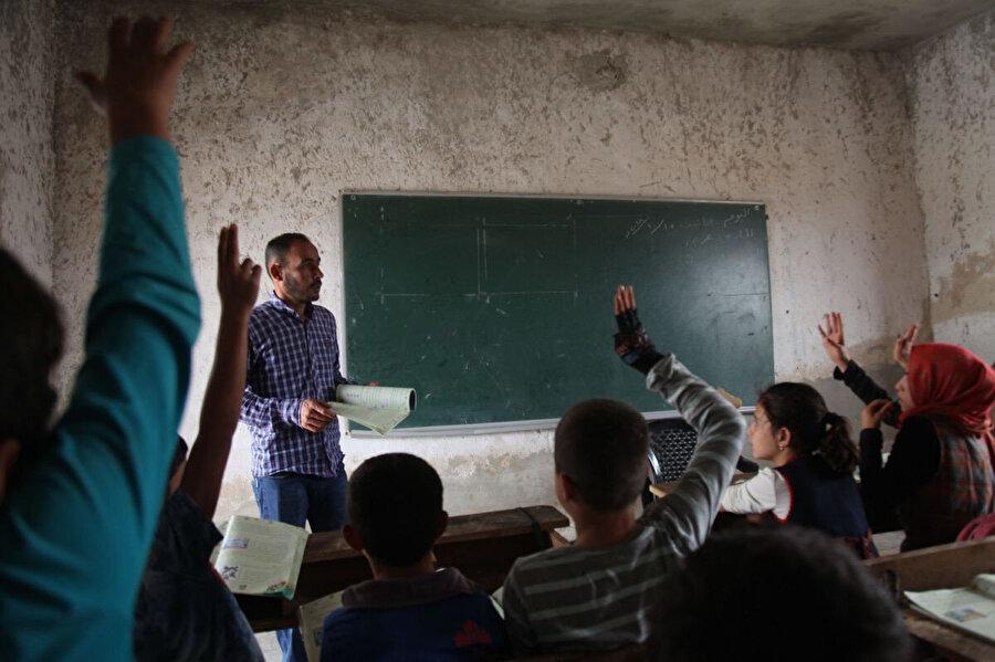 Suriye'nin İdlib kentinin kuzey kırsalında bulunan Harim kentinde bir öğretmen, öğrencilerle soru çözüyor.Suriye'nin İdlib kentinin kuzey kırsalında bulunan Harim kentinde bir öğretmen, öğrencilerle soru çözüyor.