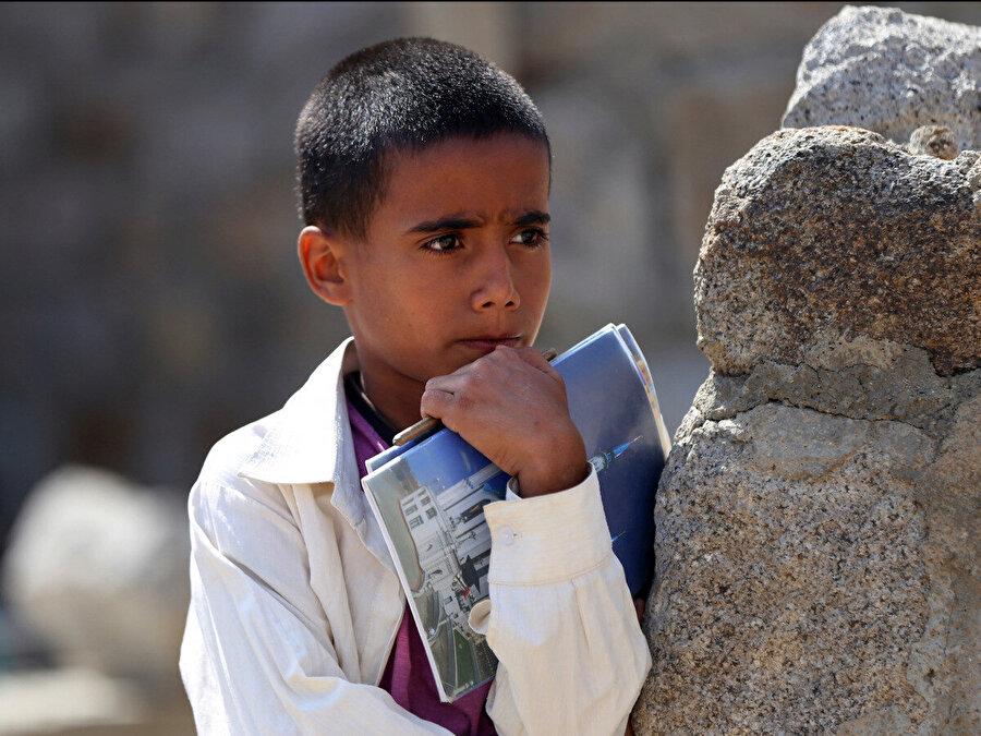 Yemenli bu çocuk, yapımı henüz tamamlanmamış okulunun yanındaki ağacın altında açık havada yapılan derse katılmak için defteri elinde bekliyor.