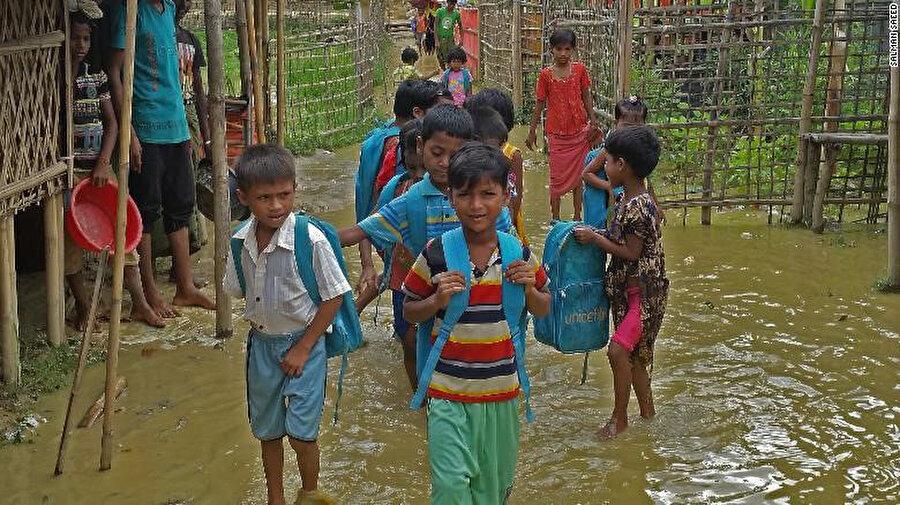 Bangladeş'teki mülteci kampındaki Arakanlı çocuklar birikmiş sel sularından geçerek kamptaki eğitim merkezlerine gidiyor.