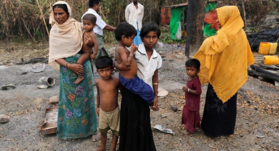 2016 yılında çekilen bu fotoğrafta, Myanmar'da yaşayan Arakanlı Müslümanlar köylerinde ateşe verilen bakkalın yanında dururken görülüyor.