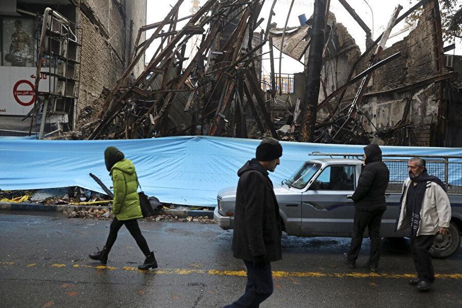 Benzin zammı protestoları sırasında ateşe verilen binanın enkazının önünden geçen İranlılar.