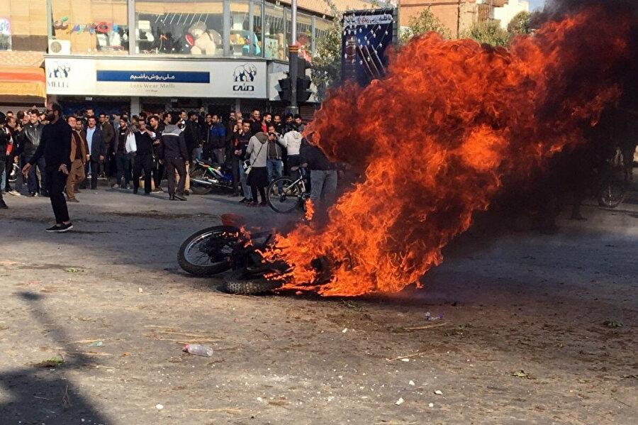 Benzin zammı protestoları sırasında İran sokaklarında ateşe verilen bir motosiklet.