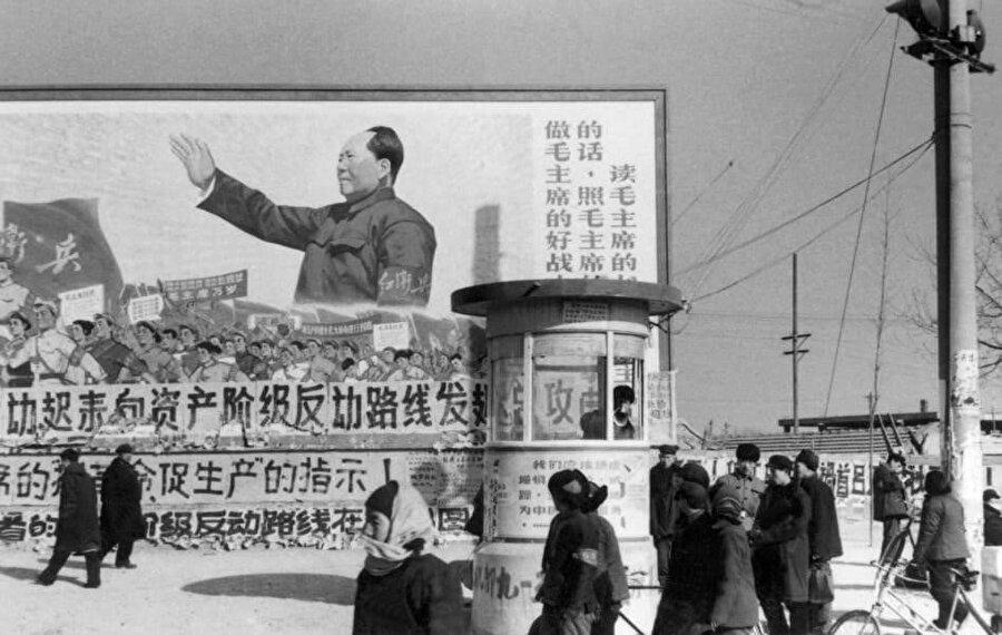 """Büyük bir Mao posterinin önünde duran Pekin halkına, """"Mao'nun iyi bir neferi olun"""" çağrısı yapılıyor."""