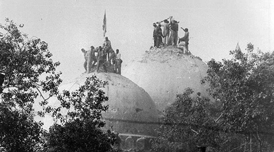 Babri Camisi'ni kubbelerini yıkmaya çalışan Hindular.