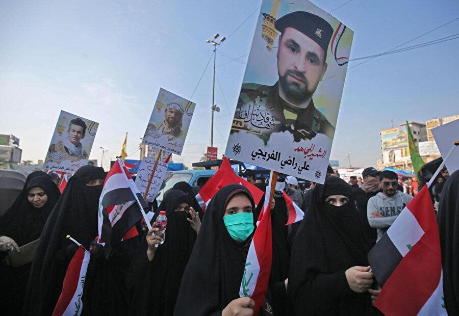 Tahrir Meydanı'ndaki protestolar sırasında çatışmalarda ölen Haşdi Şabi militanlarının posterlerini taşıyan göstericiler.