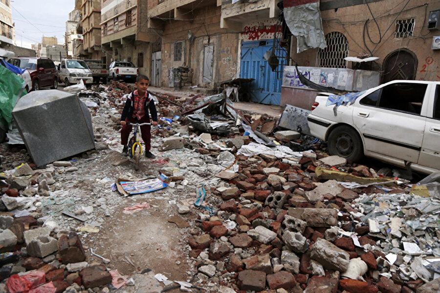 Başkent Sana'da bombalı saldırı sonrası yerle bir olan evinin enkazları arasında bisiklet süren bir Yemenli çocuk.