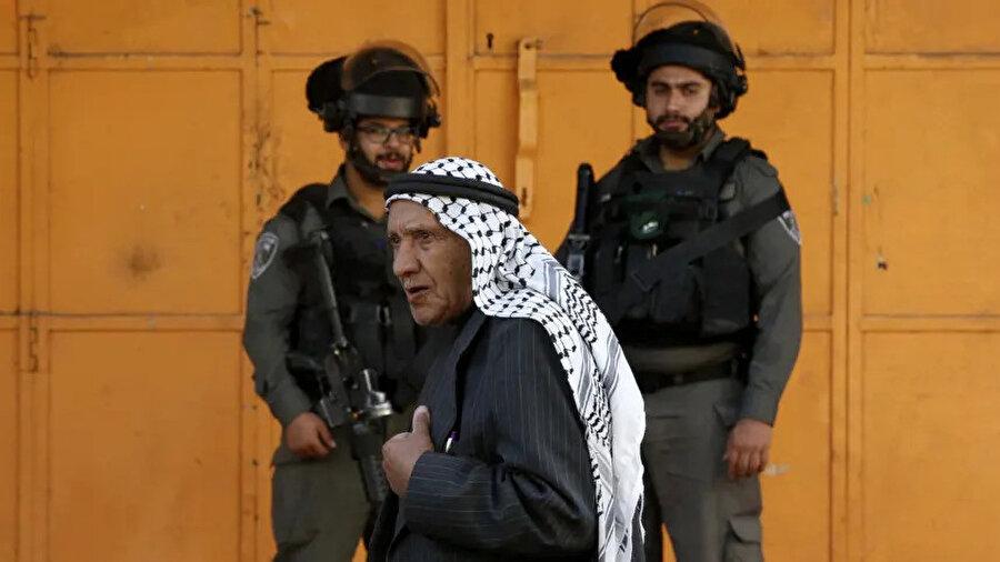 El Halil'deki bir Arap mahallesinde İsrail askerlerini önünden geçen bir Filistinli.
