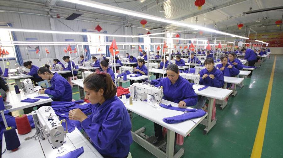 Uygur kadınlar, Çin'in Sincan Uygur Özerk Bölgesi'ndeki Hotan'ta bir fabrikada çalışırken görülüyor.
