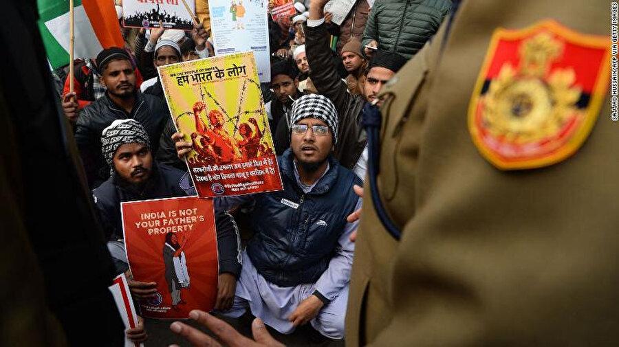 """Başkent Yeni Delhi'de polisle karşı karşıya gelen gösterilerin elindeki """"India is not your father's property."""" Hindistan babanızın malı değil"""" yazılı posterler dikkat çekti."""