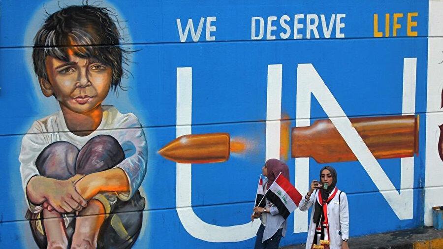 """Irak'ta gösteriler sırasında çizilen duvar resimlerinde """"Yaşamayı hak ediyoruz."""" yazılı."""