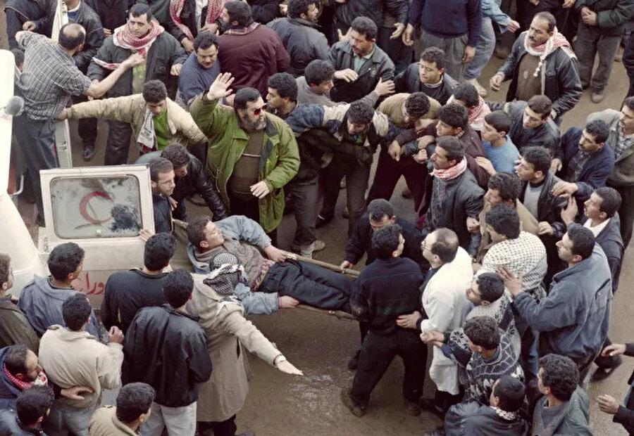 Katliam sonrası yaralıları hastaneye yetiştirmeye çalışan Filistinliler.