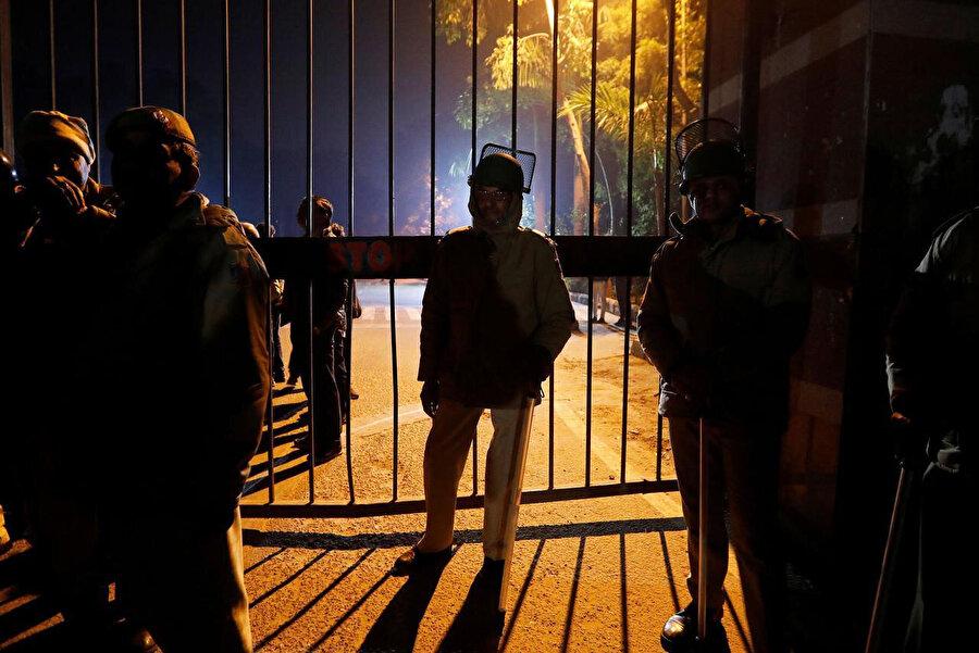 Jawaharlal Nehru Üniversitesi'nde (JNU) maskeli kişiler tarafından düzenlenen taşlı sopalı saldırı sonrası okulun kapısında bekleyen Hindistan polisi.
