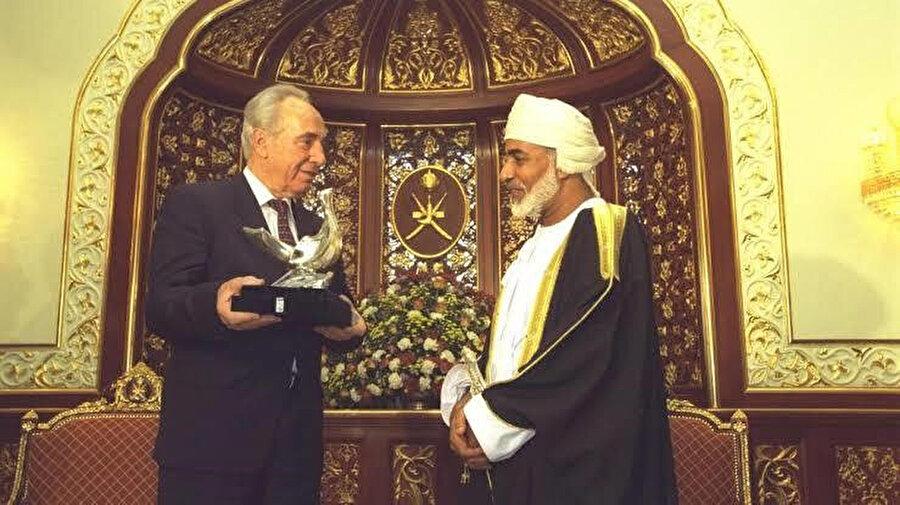 1996'da dönemin İsrail Başbakanı Şimon Perez, İsrail ile iyi ilişkiler kuran Umman Sultanı Kâbûs bin Saîd'e barış güvercini heykeli sunarken.