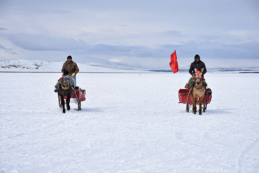 Vatandaşlar gölün üstünde atlı kızaklarla ilerliyor.
