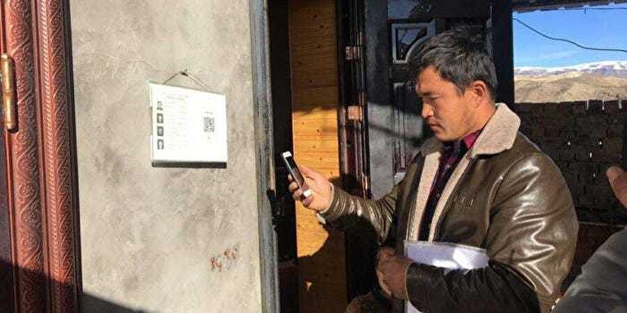 Sincan Uygur Özerk Bölgesinde bir evin duvarında asılı panodaki QR kodunu okutan hükümet yetkilisi, evin sakinlerinin kişisel bilgilerine erişebiliyor.