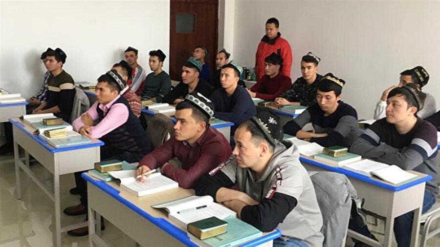 Çin'in eğitim kamplarında rızaları dışında tutularak eğitim verilen Uygurlar.