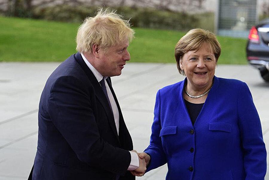 Boris Johnson ve Merkel el sıkışırken