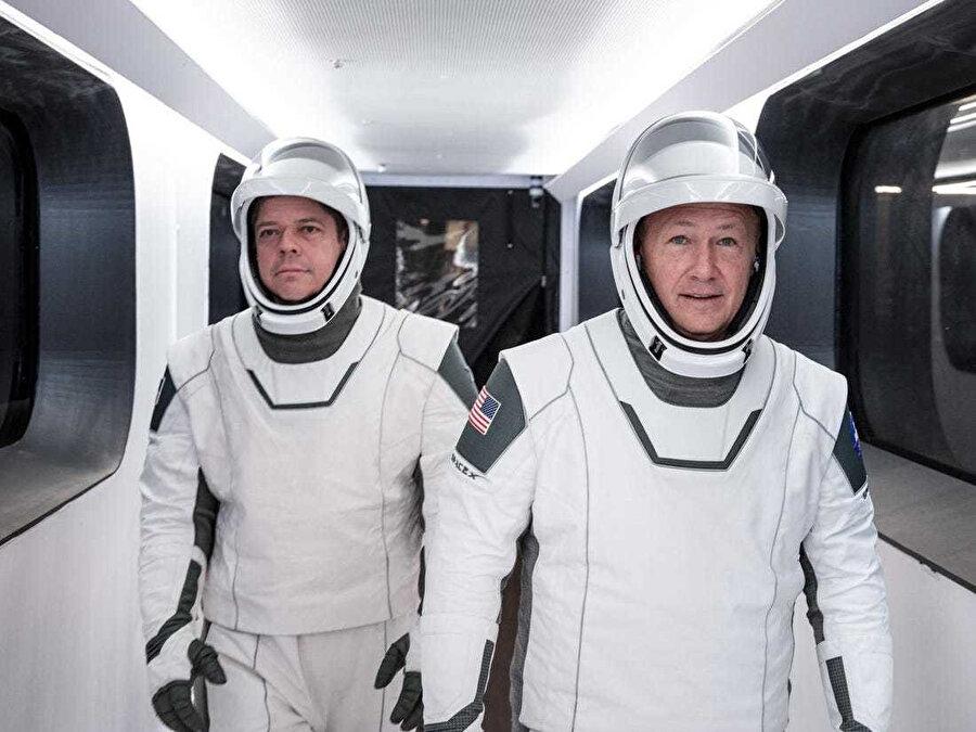 SpaceX uzay giysileri giyen Behnken (solda) ve Hurley (sağda), 17 Ocak 2020'de fırlatma kulesini SpaceX Crew Dragon uzay aracına bağlayan mürettebat koridorundan geçiyor.