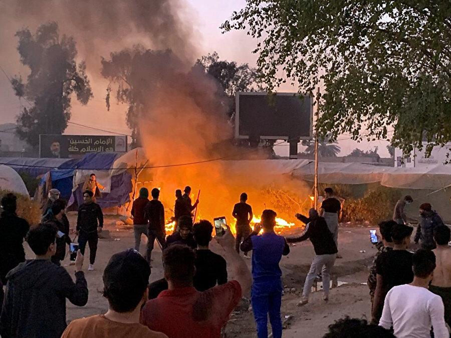 Ateşe verilen çadırlardan kurtulmaya çalışan göstericiler.