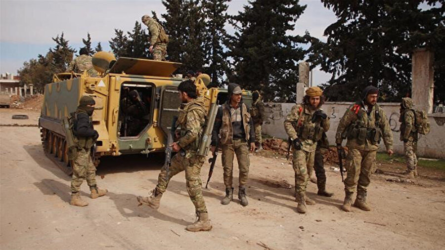İdlib'in güneyindeki bir köyde toplanan rejim karşıtı silahlı gruplar.