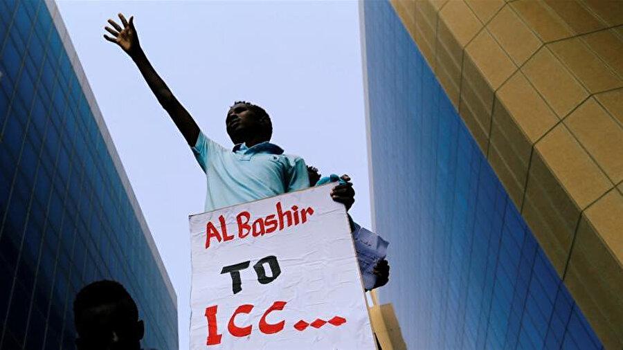 """Sudan'da Adalet Bakanlığı önünde bir gösterici """"el-Beşir, Uluslararası Ceza Mahkemesine"""" pankartıyla."""