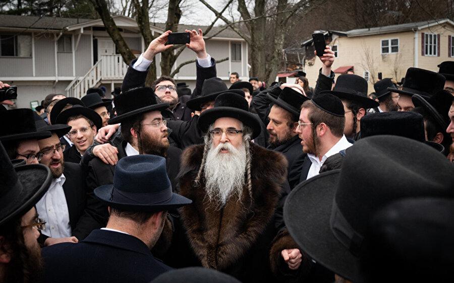 Haham Leibish Rottenberg (ortada) 5 kişinin yaralandığı saldırı sonrası evinin önünde.