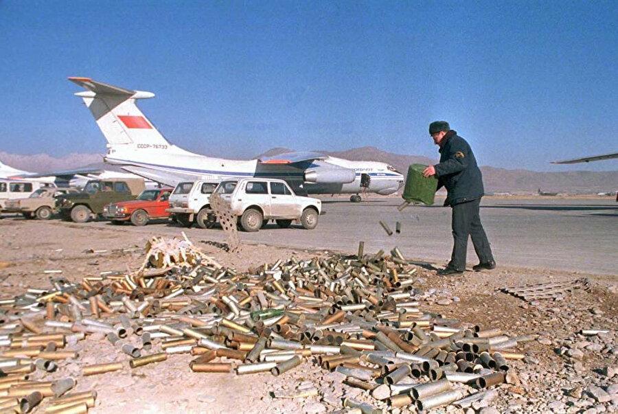 Bir Sovyet askeri Kabil Hava Üssü'nde, birikmiş uçaksavar mermi kovanlarını boşaltıyor, Ocak 1980