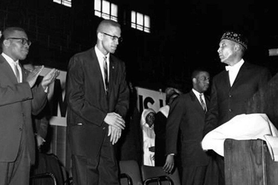 Malcolm X, Elijah Muhammed (sağda, takkeli olan) ile birlikte.