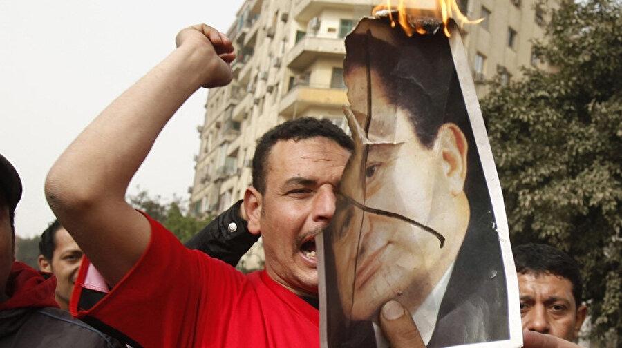Arap Baharı sürecinde Mübarek'in fotoğrafını yakan bir Mısırlı.