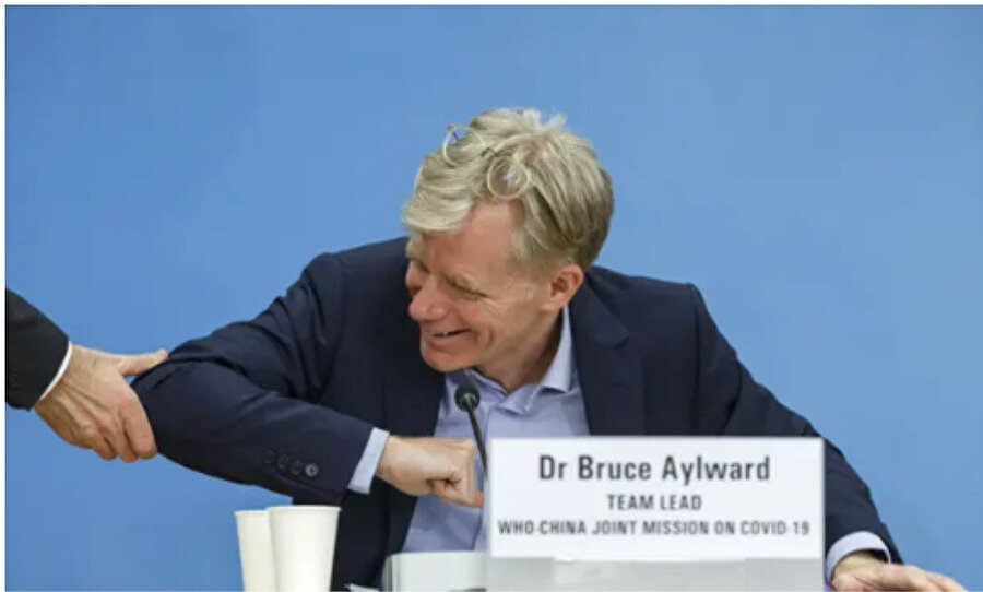 DSÖ'den Bruce Aylward dirseği ile tokalaşırken