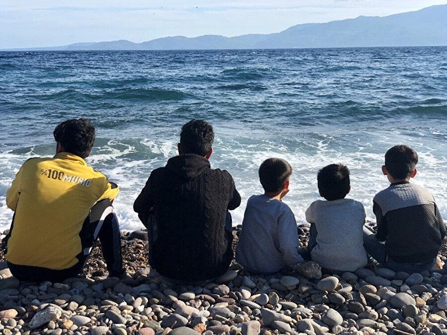Denizden Yunanistan'a geçmek isteyen çocuklar sahilde otururken görünüyor.