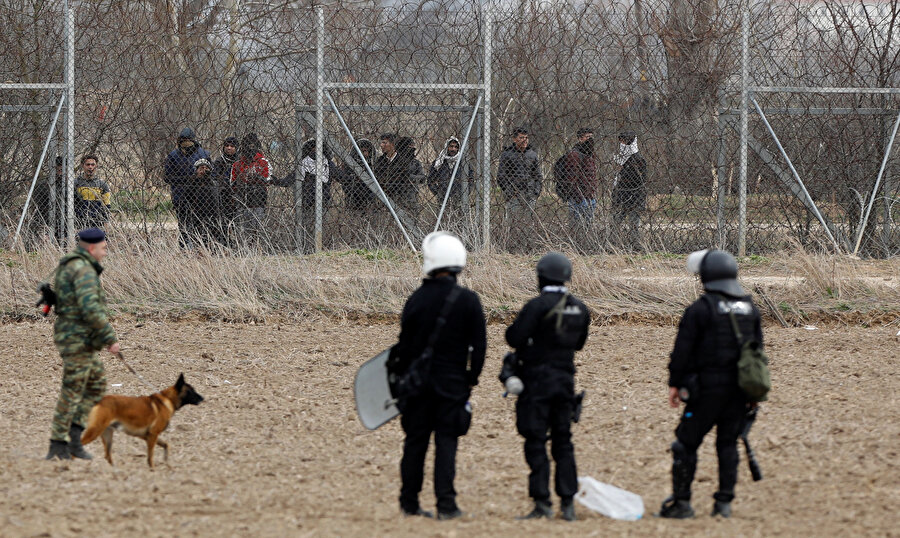 Sınır tellerinin arkasında bekleyen sığınmacılar ve güvenlik güçleri aynı karede.