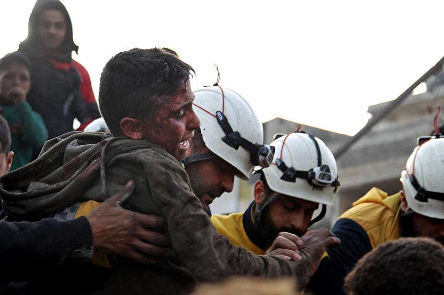 İdlib'de hava saldırısı sonrası enkazın arasından bir çocuğu kurtaran Beyaz Baretliler.