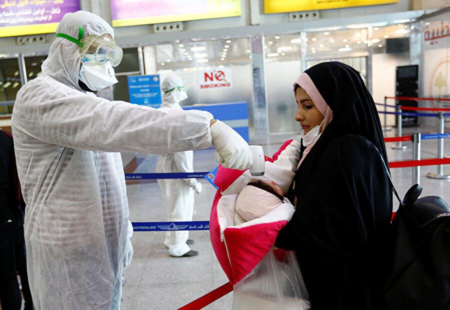 İran'da alınan tedbirler kapsamında ateşi ölçülen yolcular.