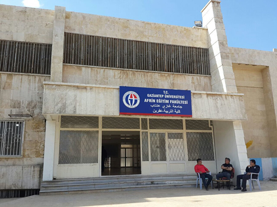 Gaziantep Üniversitesi'ne bağlı Afrin'de kurulan Eğitim Fakültesi kapısında Türk görevliler.