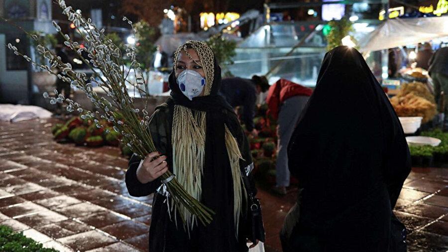 İran'da Nevruz için alışverişe çıkan kadın, koronavirüs salgınından maskeyle korunmaya çalışıyor.