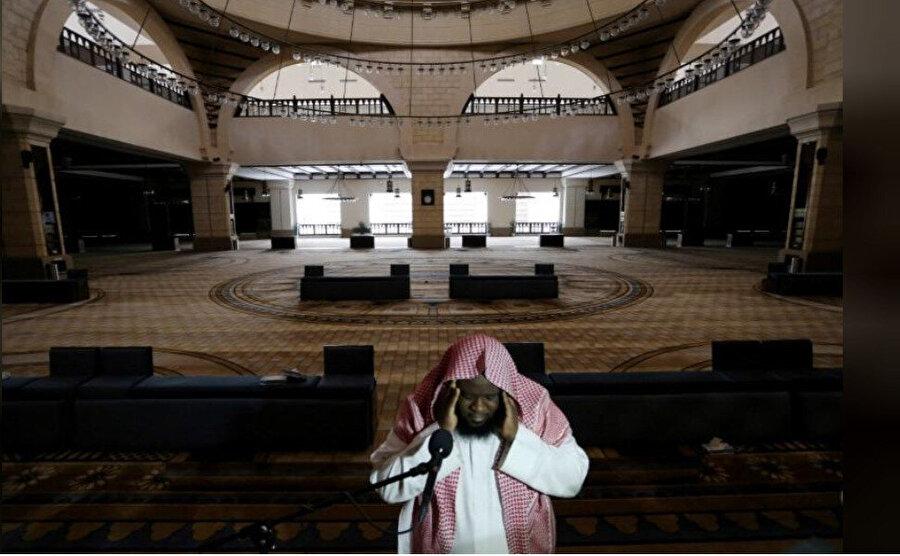 Koronavirüsün yayılmasıyla cuma namazlarının askıya alındığı Suudi Arabistan'da cemaatin olmadığı camide ezan okuyan bir müezzin.