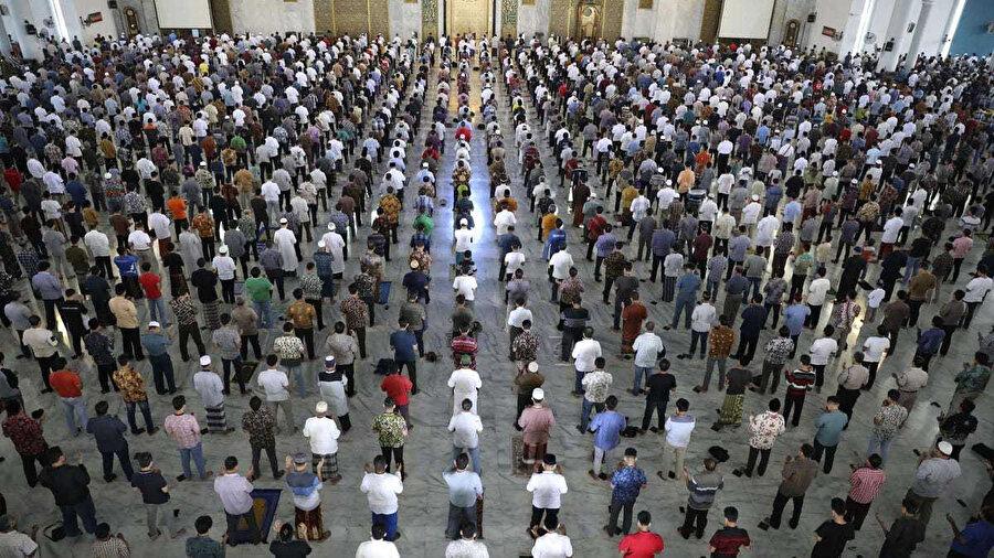 Endonezya'da koronavirüsün yayılmasını önlemek için 1 metre arayla cuma namazı kılan Müslümanlar.