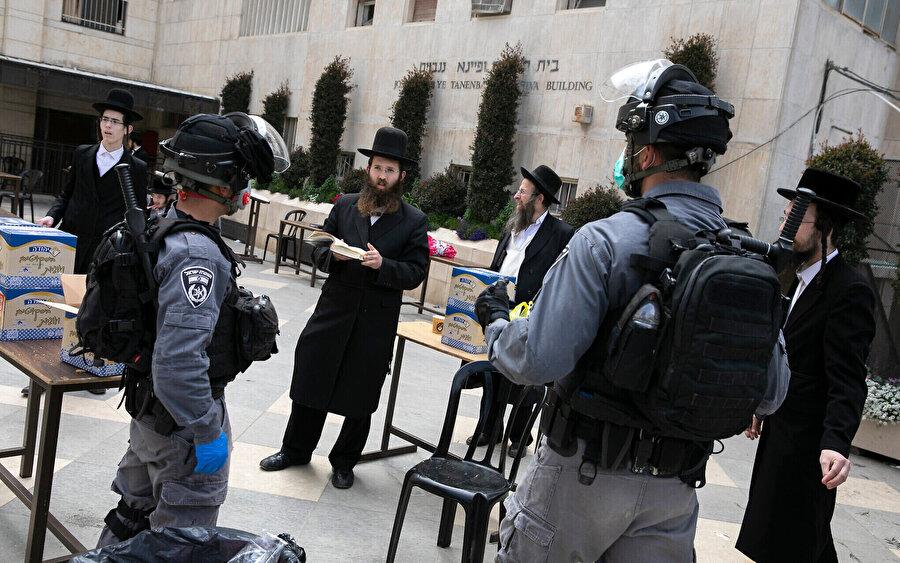 Kudüs'teki ultra-Ortodoks Mea Şearim Mahallesi'ndeki bir sinagogda polis memurları, koronavirüsün yayılmasını önlemeye yönelik kuralları ihlal ettiği için dükkanları kapatıp halka açık toplantıları dağıtmaya çalışırken görülüyor.