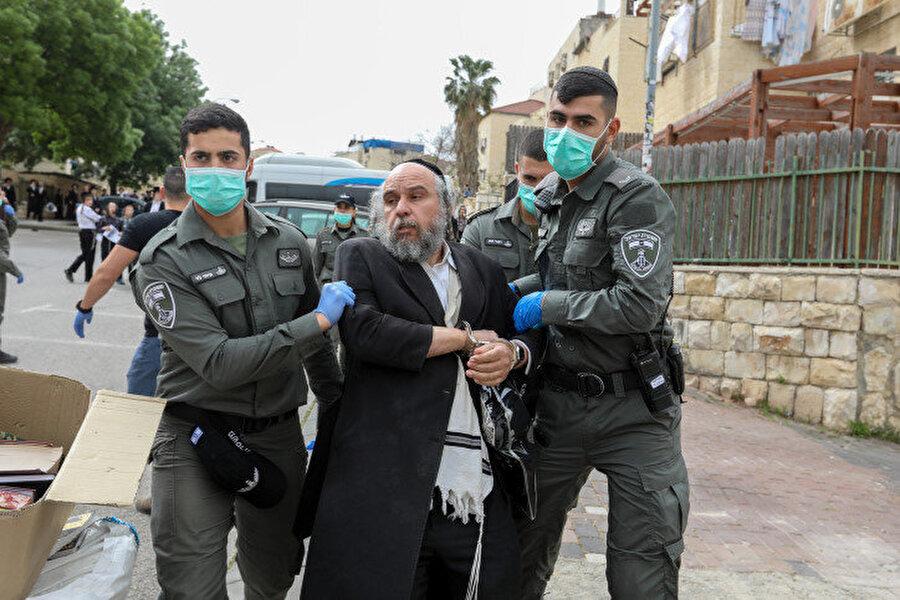Sosyal mesafe kuralına uymadığı için gözaltına alınan bir Yahudi.