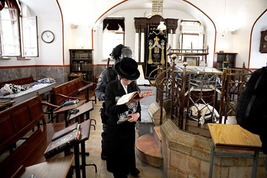 Ultra-Ortodoks Yahudi genci virüse karşı alınan önlemler kapsamında sinagogdan çıkarmaya çalışan bir polis.