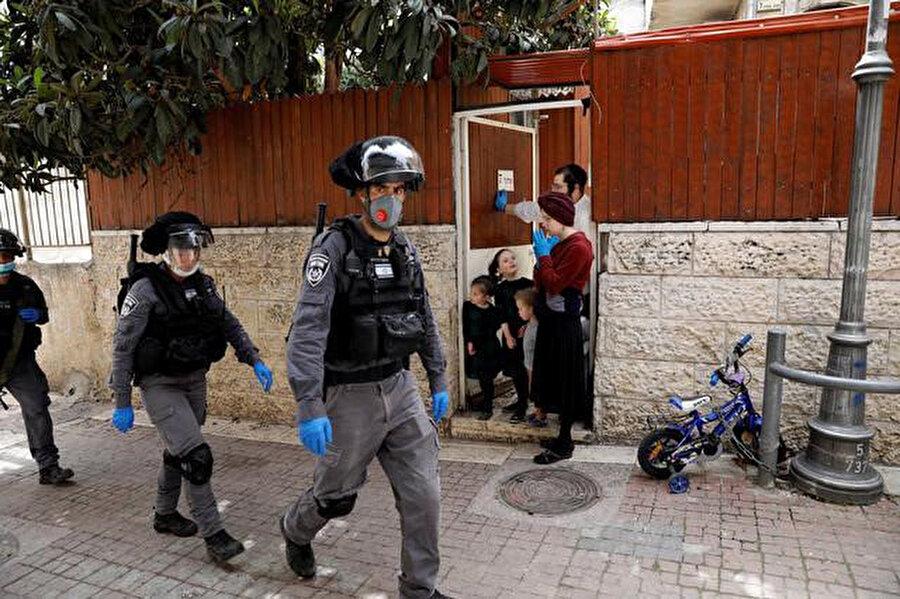 Mea Şearim Mahallesinde Ultra-Ortodoks Yahudi bir aile devriye gezen polisleri izliyor.