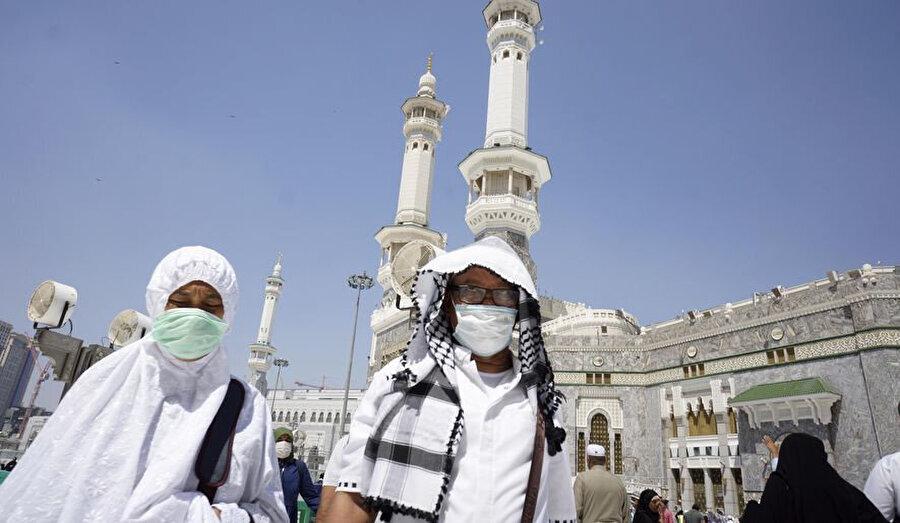 Yasaklar başlamadan önce Mescid-i Haram'da maskeyle ziyaretlerini sürdüren Müslümanlar.